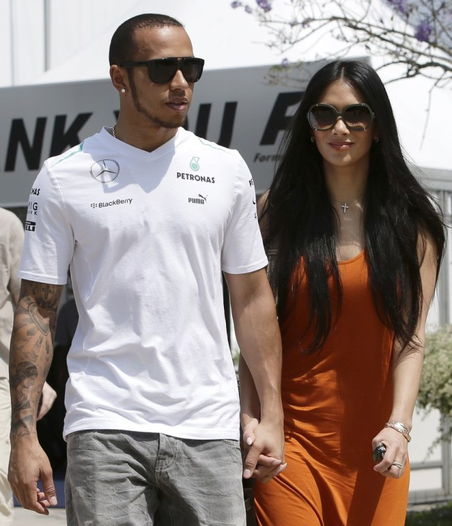 Mercedes Formula One driver Hamilton walks with girlfriend Scherzinger in the paddock before the start of the third practice session of the Malaysian F1 Grand Prix at Sepang International Circuit outside Kuala Lumpur